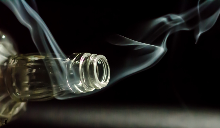 photo of bottle with incense smoke