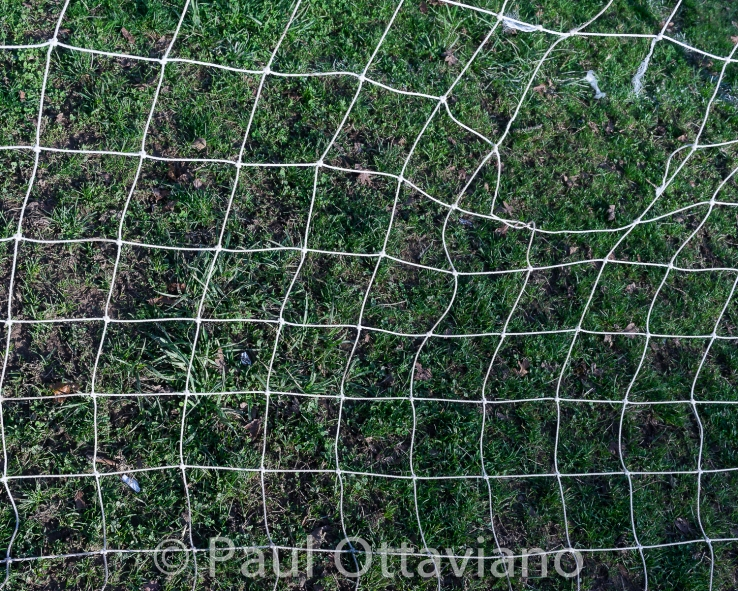 photo of soccer net with a hole in it by paul ottaviano