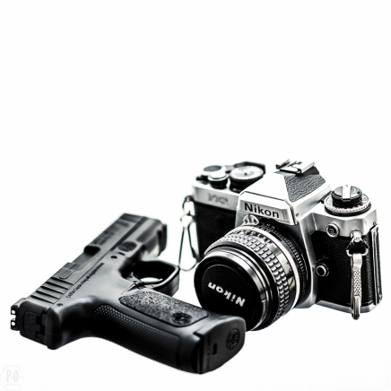 black and white image of pistol and film camera