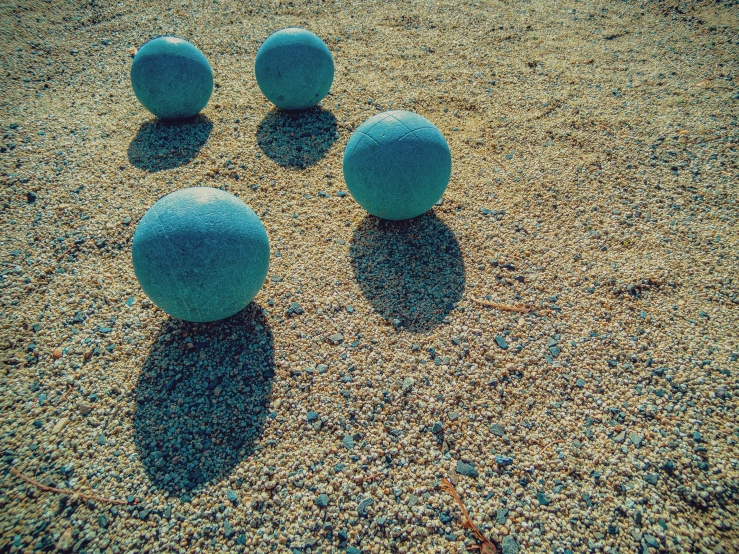 blue bocce balls and shadows on sand court